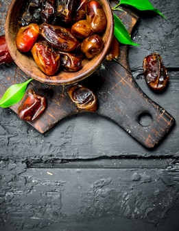 Dates with a bowl with green leaves on black rustic table.