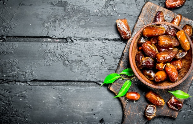 Dates with a bowl with green leaves on black wooden table.