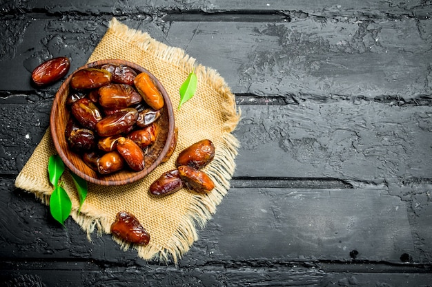 Dates with a bowl with green leaves on rustic table.