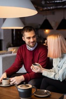 デートのコンセプトカフェでお茶を飲む若い幸せなロマンチックな愛情のあるカップル