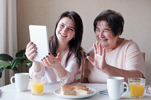 娘と年配のお母さんがビデオ接続を介して友達とチャット