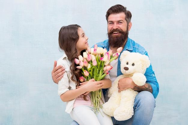娘と父は誕生日を祝います。父の日とお父さんに挨拶する女の子。テディベアと幸せな家族の肖像画。春の花の花束。女性の日。母の日のためにチューリップを準備します。