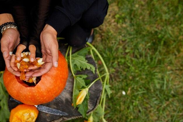 Дочь и отец руки, которые вытаскивают семена и волокнистый материал из тыквы перед резьбой на хэллоуин. готовит джека фонаря.