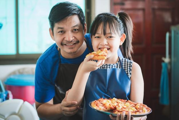 娘とお父さんが一緒にキッチンで楽しくピザを作っています。家族料理のコンセプト