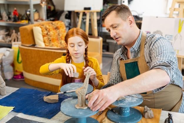 Дочь и отец лепят глиняных животных в мастерской
