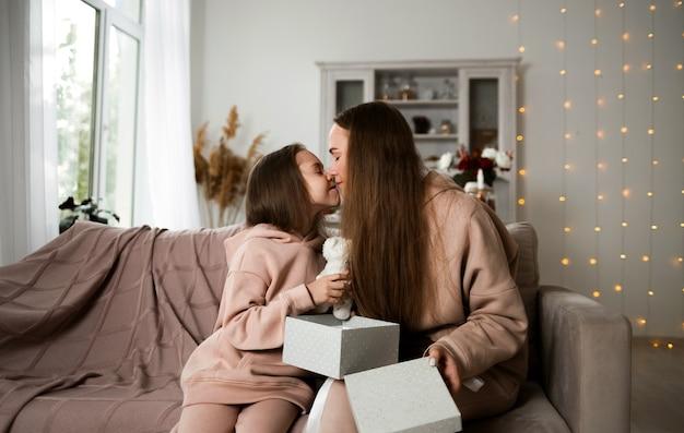 娘とお母さんは、オープンギフトとキスをしてソファに座っています