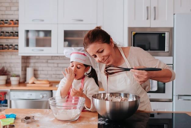 母の日のおいしいデザートを家で料理する娘と母