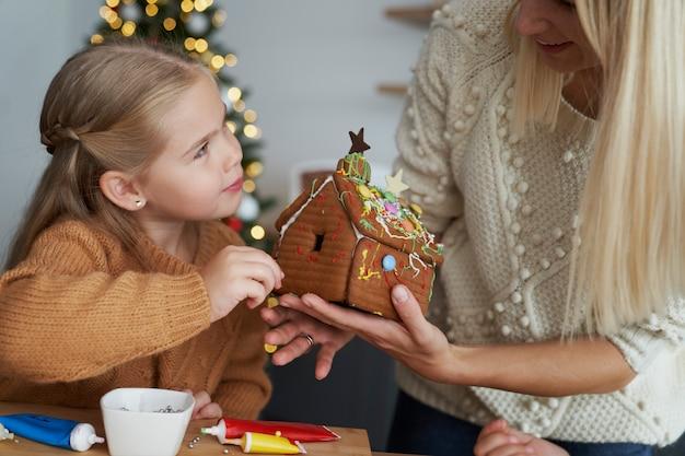 ジンジャーブレッドハウスを飾る娘と母