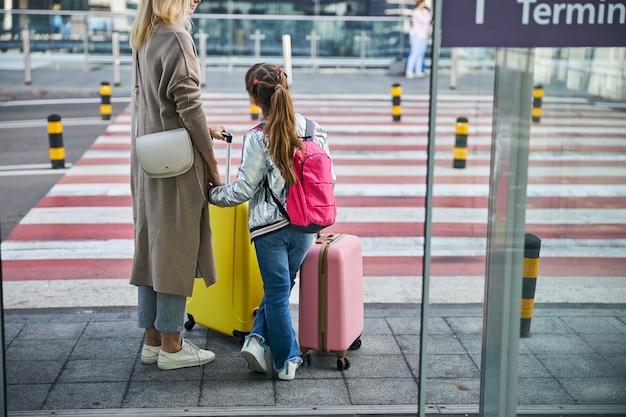 道路の前でバッグを持っている娘と母