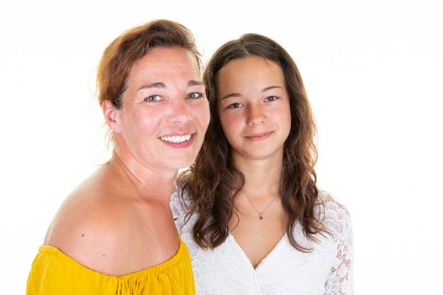 Дочь и мать обнимали друг друга на белом фоне