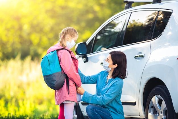 学校の前に仮面の娘と母親