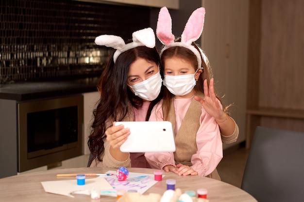 의료 마스크를 쓴 딸과 어머니는 태블릿 장치를 사용하여 친척에게 비디오 메시지를 보냅니다. 가족 격리 온라인에서 집에서 부활절을 축하