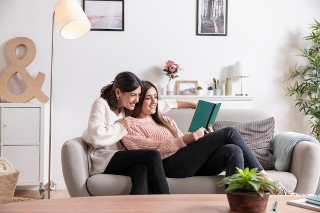 Дочь и мать на диване чтении