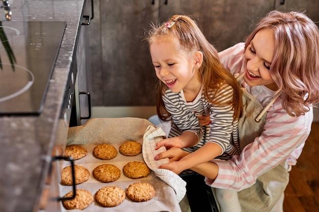 Дочь и мать достают поднос с печеньем из духовки на кухне