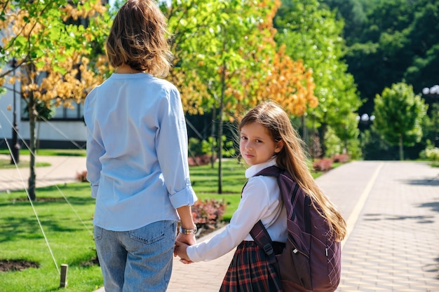 娘と母が一緒に通りを歩いて学校に行く