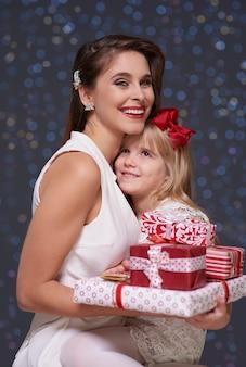 プレゼントの山を持つ娘と母