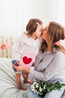 Дочь и мама с поздравительной открыткой целуются
