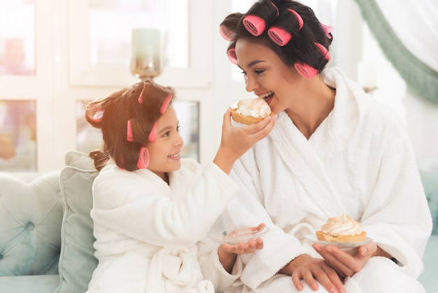 Daughter in bathrobes is feeding her mother a cake