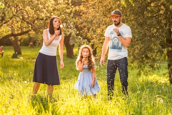 Daughter blowing dandelion with her parents