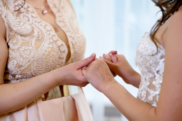 Daughter of the bride and mother holding hands.