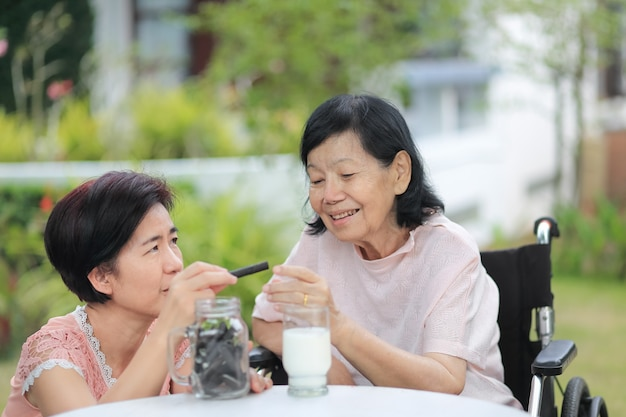 Daughter caring for the elderly asian woman