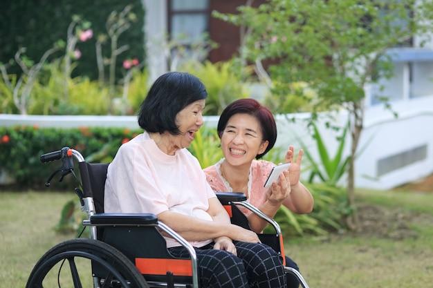 高齢のアジアの女性の世話をする娘
