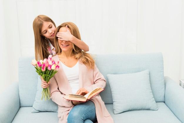 Дочь закрывает глаза маме и дарит тюльпаны