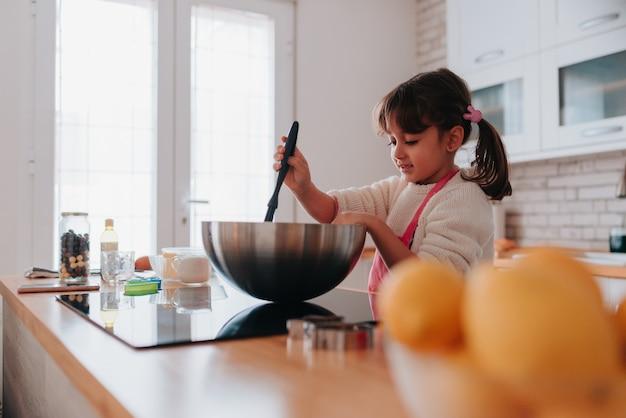 Дочь готовит шоколадный десерт, чтобы подарить маме на день матери