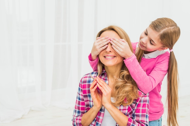 Daughter covering eyes of mother