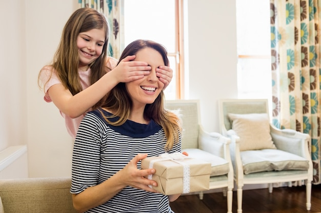 Daughter covering her mother eyes in living room