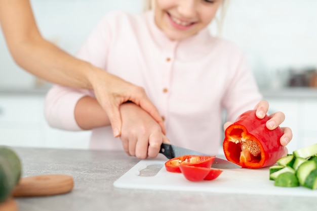 Daughter cutting peppers helped by her mother