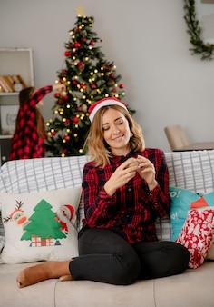 ソファに座って、家でクリスマスの時間を楽しんでいるサンタの帽子でクリスマスツリーと母を飾る娘