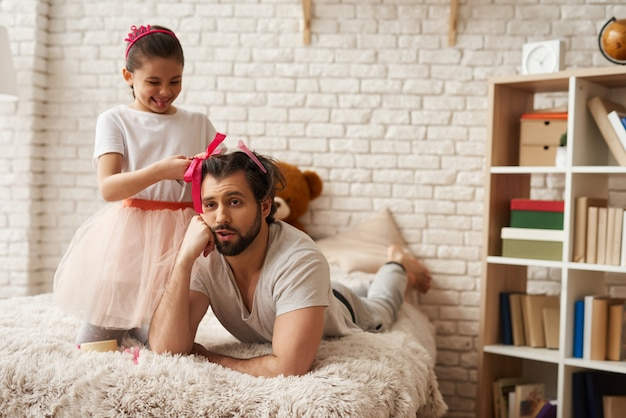 Daughter doing hairstyles to her father in bedroom
