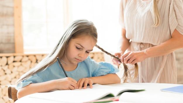Дочь делает домашнее задание дома, пока мама заплетает ей волосы