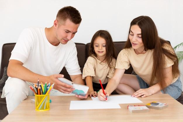 Дочь рисует с родителями