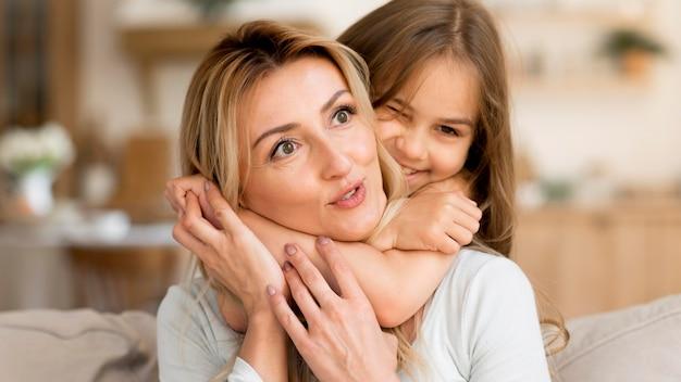 家で母親を抱きしめる娘