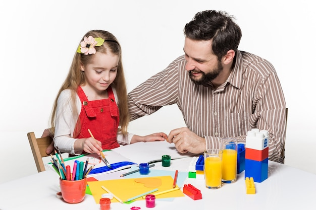 The daughter and father drawing and writing together on white background