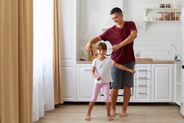Figlia e padre che si divertono e ballano in cucina, persone che indossano abiti casual, uomo che alza le trecce da bambina, famiglia felice che trascorre del tempo insieme a casa.