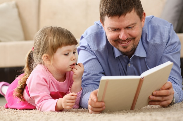 Daughter father reading book lying on carpet