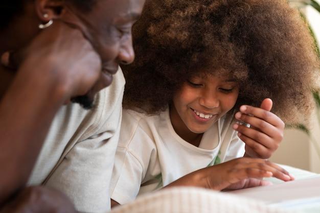 Figlia e padre che leggono un libro insieme Foto Gratuite