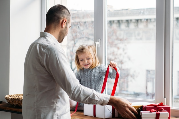Daughter and father unpacking presents near window