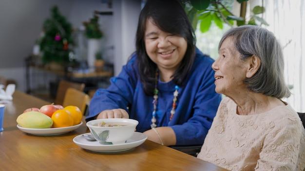 Дочь кормит пожилую мать супом.