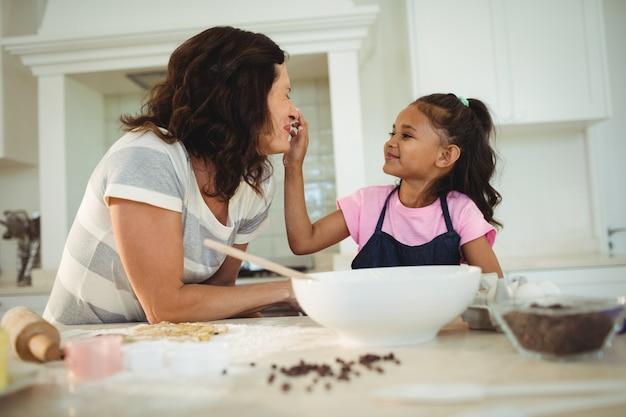 Дочь кормит мать во время приготовления печенья