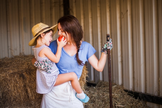 Daughter feeding red apple to her mother standing in the barn