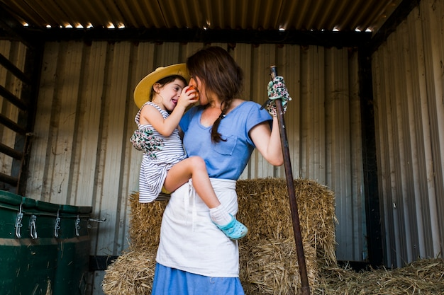 Daughter feeding red apple to her mother standing in front of hay stack