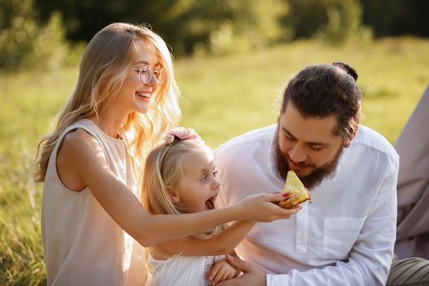 Дочь кормит папиной пирог. счастливая семья на летнем пикнике. размытый фон
