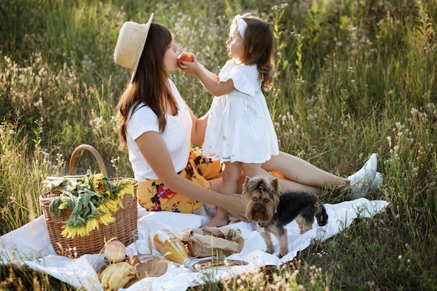 Daughter feeds her mother fruit in the summer at a picnic