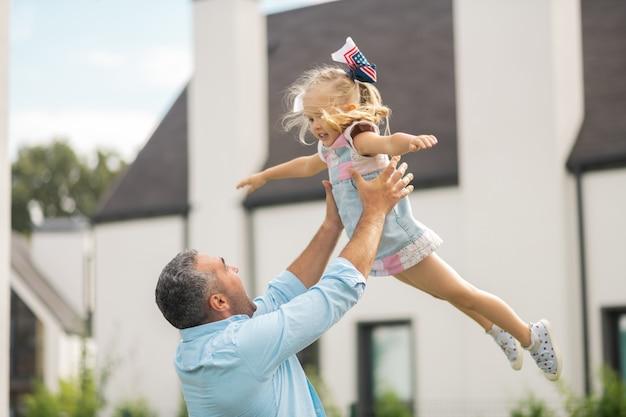 飛んでいる娘。彼女のパパと楽しみながら空を飛んでいるかわいい金髪の娘