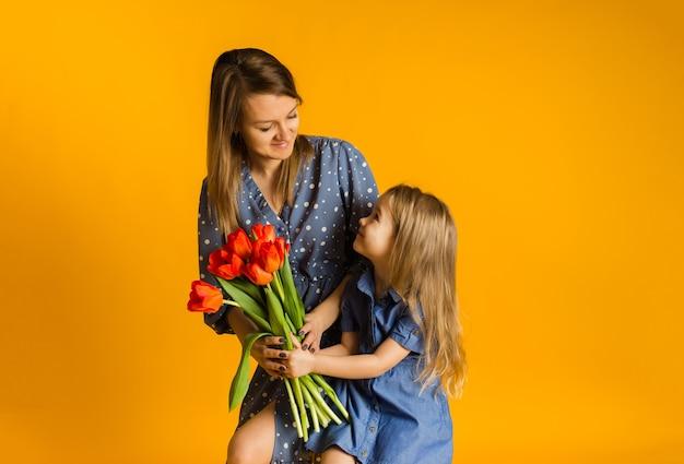Дочь дарит маме букет красных тюльпанов на желтой стене