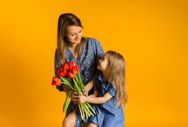 Daughter gives mother a bouquet of red tulips on a yellow wall